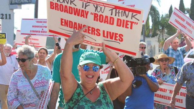 "A large crowd showed up at the intersection of Broadway and Cherry Ave late Monday afternoon to protest the newly installed ""road diet."""